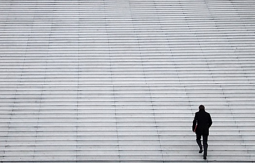 picture of man walking up a column of steps
