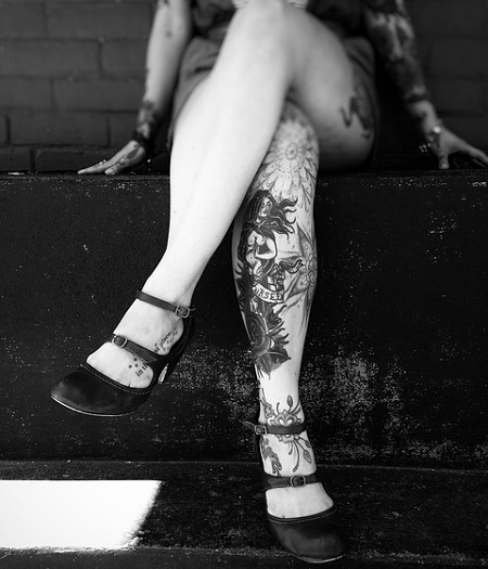 a picture of a young lady with tattoos sitting on a concrete ledge
