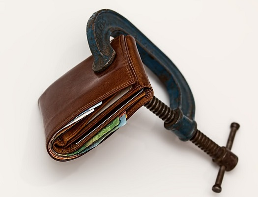 a picture of a vice clamping down on a wallet
