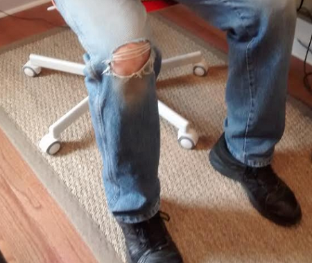 a picture of Mr. Groovy's jeans with a hole in the right knee