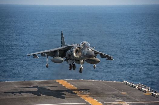 a picture of a fighter jet landing on an aircraft carrier