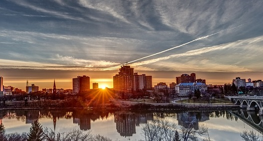 a picture of the sun setting on the skyline of Saskatoon