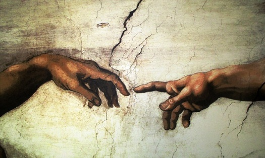 a picture of two index fingers about to touch in Michaelangelo's famous creation painting
