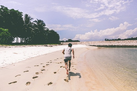 A picture of a man running on the beach