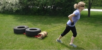 A picture of Amy dragging a weighted down toboggan