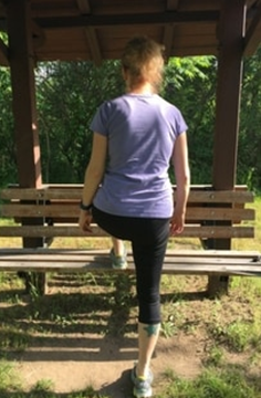 A picture of Amy stepping up on a park bench