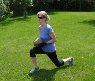 A picture of Amy doing lunges holding a large rock
