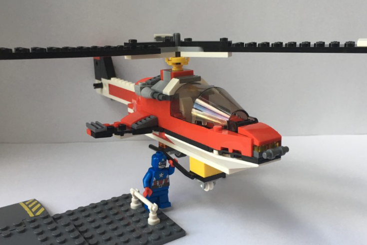 A picture of a Lego helicopter being lifted by a Lego Captain America