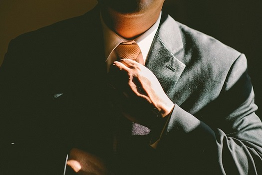 A picture of a man adjusting his tie and looking very confident
