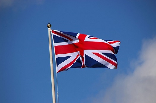 a picture of a flag pole with the union jack waving in the wind