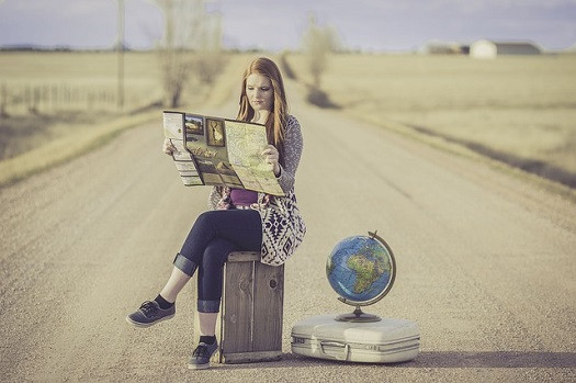 a picture of a woman sitting in the middle of a dirt road, reading a map