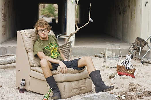 a picture of a young homeless man, sitting on a couch in an outdoor homeless camp