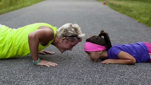 a picture of a mother and daughter doing push ups