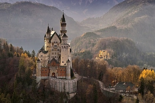 a picture of a castle nestled in European mountains