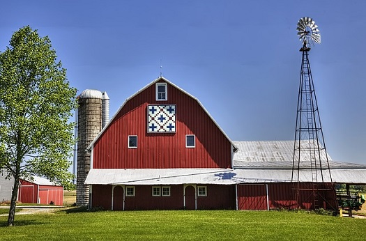 a picture of a barn with a silo and a windmill